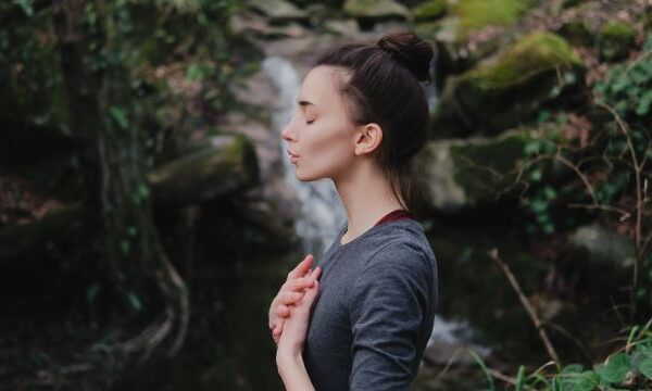 Picture of a woman deep breathing by a waterfall.