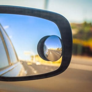 Close up picture of a car side view mirror with a small circular mirror to help eliminate blind spots